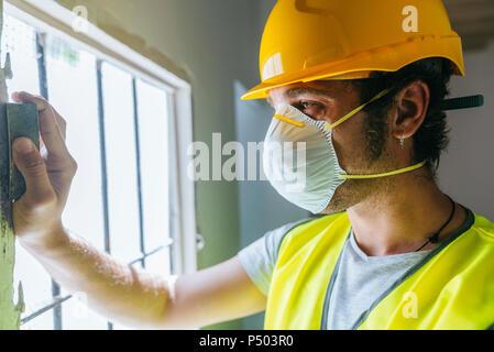 Close-up of worker sanding wooden window - Stock Photo