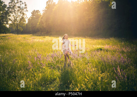 Smiling girl running on flower meadow at evening twilight - Stock Photo