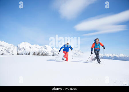 Austria, Tyrol, snowshoe hikers running through snow - Stock Photo