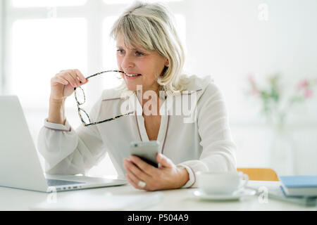 Mature businesswoman holding cell phone working on laptop at desk - Stock Photo
