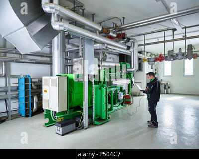 Combined heat and power plant, worker using laptop in front of gas engine - Stock Photo