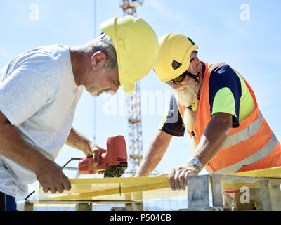 Construction worker cutting plywood with jigsaw on construction site - Stock Photo