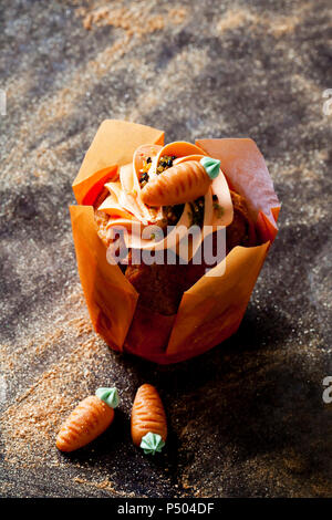 Carrot cup cake garnished with  cream topping, sugar granules and marzipan carrot - Stock Photo