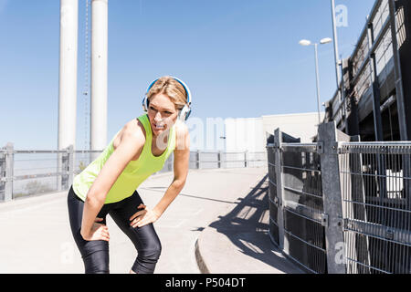 Woman jogging in the city, taking a break - Stock Photo
