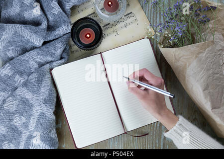 Hand of woman writing in notebook