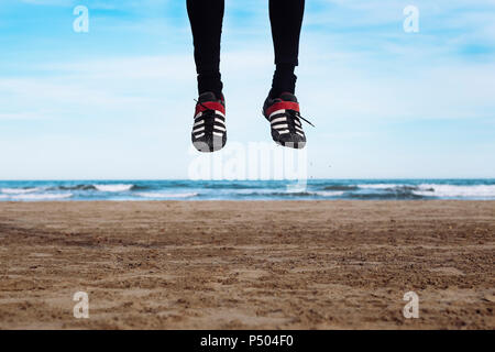 Legs of man jumping in the air on the beach - Stock Photo