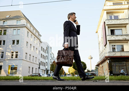 Mature businessman walking and using smartphone in the city - Stock Photo