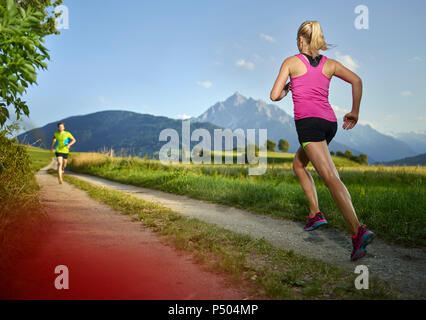Young woman running on field path - Stock Photo