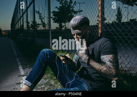 Tattooed young man with earbuds and smartphone smoking a cigarette at wire mesh fence - Stock Photo