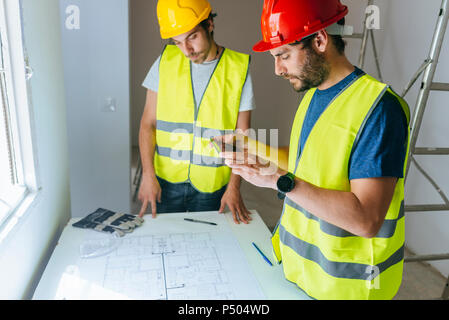 Workers taking a picture of the plan with mobile phone - Stock Photo