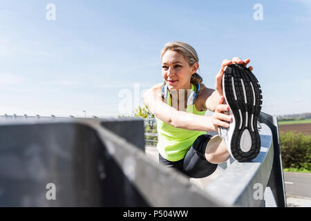 Woman jogging in the city, taking a break, stretching - Stock Photo