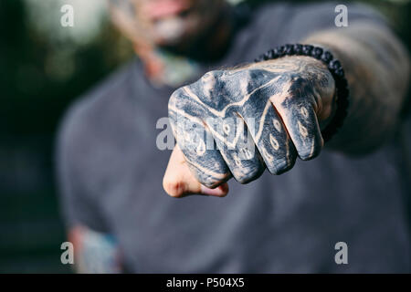 Close-up of clenched fist of tattooed young man outdoors - Stock Photo