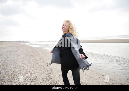 Netherlands, portrait of blond young woman running on the beach - Stock Photo