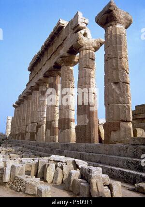 Greek art. Selinunte Acropolis. Temple C. Built in the mid-sixth century b.C. Has a perimeter of 42 columns, 12 of which still remain standing. Colonnade. Sicily. Italy. - Stock Photo