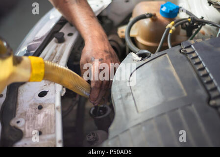 Car mechanic changing engine oil in a dirty engine - Stock Photo