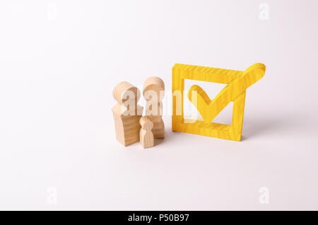 Wooden figures of people stand near the tick in the box. Checkbox. People vote in elections, a referendum. Democratic process, participation in govern - Stock Photo