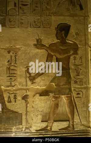 Ptolemaic temple of Hathor and Maat. Polychrome reliefs that decorate the interior. Pharaoh making offerings and libations. Deir el-Medina. Egypt. - Stock Photo