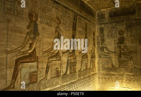 Ptolemaic temple of Hathor and Maat. Polychrome reliefs that decorate the interior. Seated gods. Deir el-Medina. Egypt. - Stock Photo