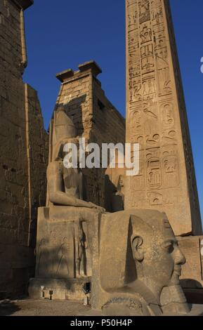 EGYPT. TEMPLE OF LUXOR. Partial view of the first pylon of the temple, the remains of an obelisk of pink granite, and head and colossal statues of Ramses II. Ancient Thebes 'Waset,. - Stock Photo