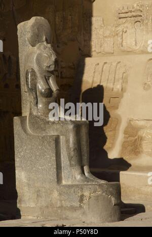 Goddess Sekhmet, goddess of war, represented with head of a lioness and the human body and crowned with the solar disk. Sculpture in the mortuary temple of Ramses III (1187-1156 BC). New Kingdom. Medinet Habu. Egypt. - Stock Photo