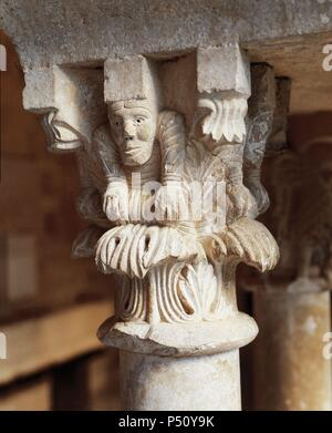 Spain. Girona. Abbey of Saint Peter of Galligants. Cloister.  Romanesque. 12th century. Capital depicting a man resting his hands on his knees. - Stock Photo