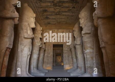Egyptian art. Great Temple of Ramses II (1290-1224 BC). Funerary temple carved in the rock. View from inside the first room, with eight statues of Ramses II as the god Osiris. Abu Simbel. Egypt. - Stock Photo