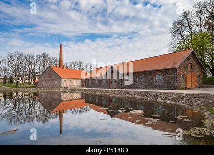 Old Olustvere manor park in the summer time. The manor's vodka distillery buildings are reflected in the park's pond. located in the middle of Estonia - Stock Photo