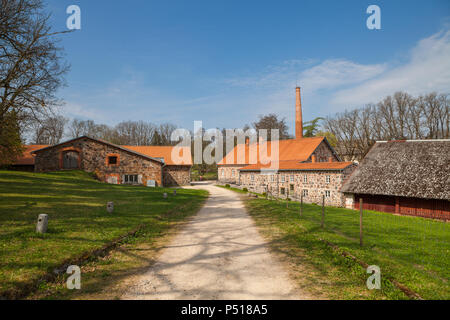 Old Olustvere manor park in the summer time. The manor's vodka distillery buildings located in the middle of Estonia - Stock Photo