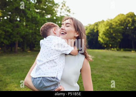 Mother and son are hugging in the park.  - Stock Photo