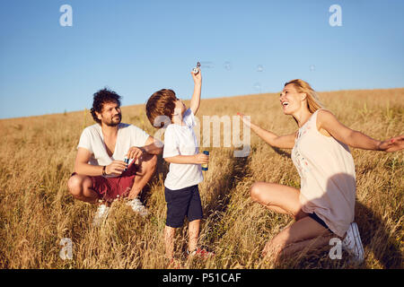 The family is playing with soap bubbles in nature - Stock Photo