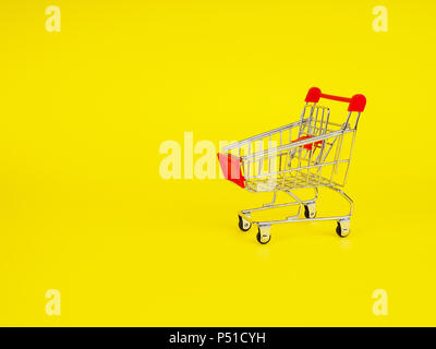 supermarket trolley on yellow background, empty, Concept of shopping. Copy space for advertisement - Stock Photo