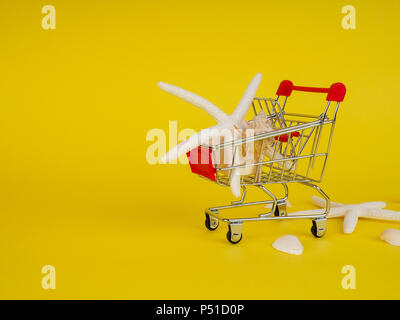 supermarket trolley on yellow background, shells inside, release, Concept of shopping. Copy space for advertisement - Stock Photo