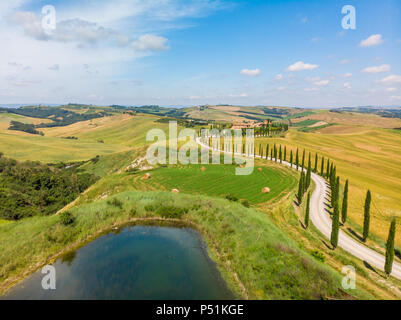 Beautiful landscape scenery of Tuscany in Italy - cypress trees along white road - aerial view -  close to Asciano, Tuscany, Italy - Stock Photo