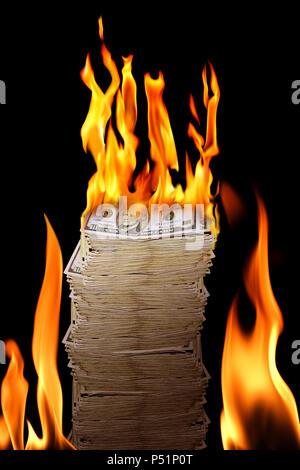 close up shot of burning money pile over black background - Stock Photo
