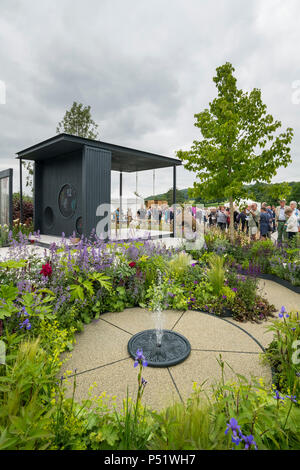 People viewing seating in pavillion, water feature & flowering plants - CCLA : A Family Garden, RHS Chatsworth Flower Show, Derbyshire, England, UK. - Stock Photo