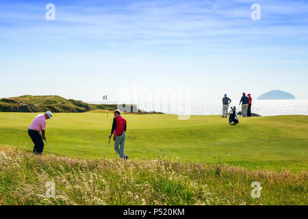 Golfers playing on the newly redesigned 9th putting green called Bruces Well at the Ailsa Course of Trump Turnberry with the Firth of Clyde and Ailsa  - Stock Photo