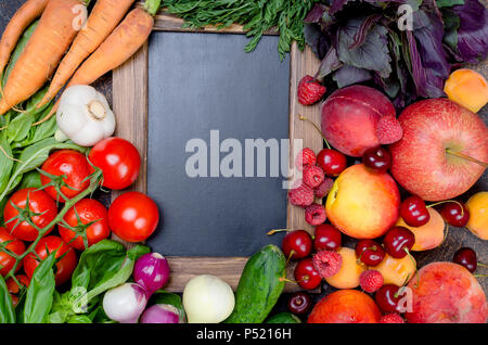 many mixed different seasonal vegetables, fruits and berries around an empty black frame, top view, copy space - Stock Photo