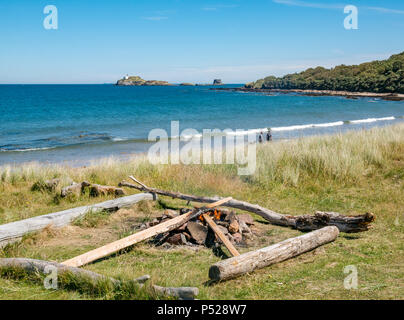 John Muir Way, East Lothian, Scotland, UK, 24th June 2018. UK Weather: A warm sunny day during the 2018 Summer heatwave brought people to the coast for leisure pursuits. Campers lit a fire near the beach with a view of the lighthouse on Fidra Island, reputedly the inspiration for Robert Louis Stevenson's novel Treasure Island - Stock Photo