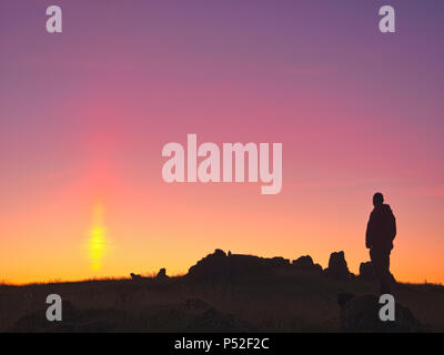 Brassington, Derbyshire, UK. 24th June, 2018. Weather UK: person watching the sun pillar solar column during an amazing sunset at Harborough Rocks near Brassington & the High Peak Trail, Derbyshire, Peak District National Park Credit: Doug Blane/Alamy Live News - Stock Photo
