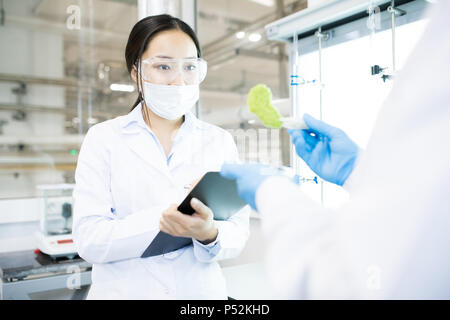Scientist showing colleague green vegetable sample - Stock Photo