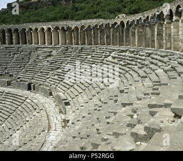 ARTE ROMANO. ASIA MENOR. TURQUIA. TEATRO DE ASPENDOS. Adosado a la colina, es uno de los teatros mejor conservados de la antigüedad romana. Erigido por el arquitecto Zenón, hacia el 170 d. C., bajo reinado de Marco Aurelio. Vista de las GRADAS SUPERIORES y la GALERIA ABOVEDADA que se apoya sobre los pilares. Península Anatólica. - Stock Photo