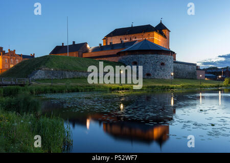 Beautiful view of lit 13th century Häme Castle and its reflections on lake Vanajavesi in Hämeenlinna, Finland, in the evening. - Stock Photo
