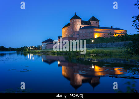 Beautiful view of lit 13th century Häme Castle and its reflections on lake Vanajavesi in Hämeenlinna, Finland, at night. - Stock Photo