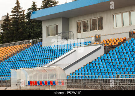 Empty bright seats in stadium and football gate - Stock Photo