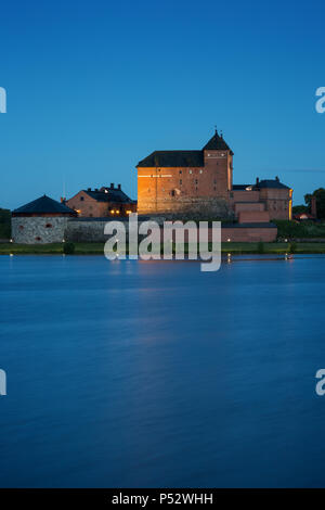 Beautiful view of lit 13th century Häme Castle and lake Vanajavesi in Hämeenlinna, Finland, in the evening. - Stock Photo