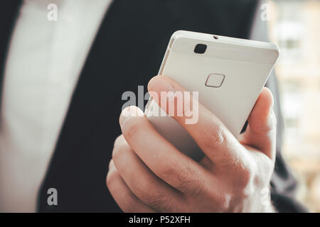 A Macro Of A Businessman Using A Smartphone In Front Of A Bright Background - Stock Photo