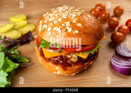 homemade hamburger with pork and ketchup on a wooden table - Stock Photo