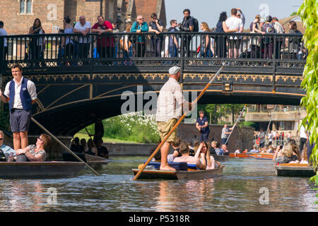 People on punt boats punting on the river Cam as people walk along a bridge, on a sunny Summer afternoon, Cambridge, UK - Stock Photo