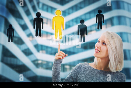 Beautiful blonde woman pointing her finger up choosing a different people icon. Employee choice, group leadership concept. Select the right workforce  - Stock Photo
