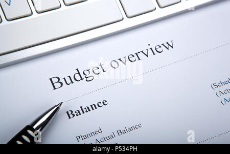 document with title budget overview and keyboard close up - Stock Photo